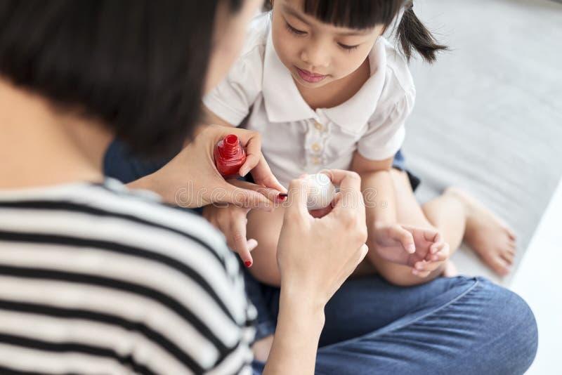 Sch?ne junge Mutter malt den Nagellack zu ihrer netten kleinen Tochter stockfoto