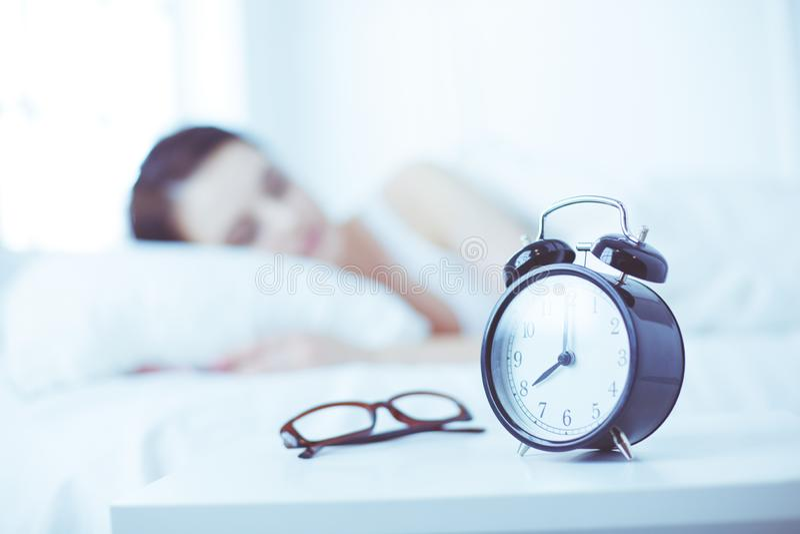 Sch?ne junge schlafende Frau beim im Bett auf dem Hintergrund des Weckers bequem und himmlisch liegen lizenzfreie stockfotos