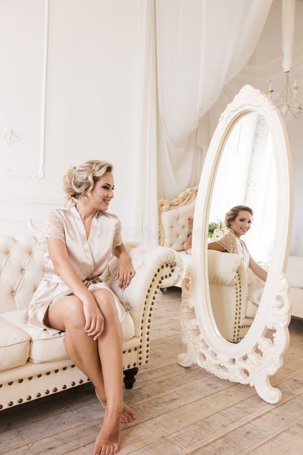 Sch?ne junge sexy Blondine in einer Seidenrobe, die auf einem Sofa vor dem Spiegel sitzt lizenzfreie stockfotografie