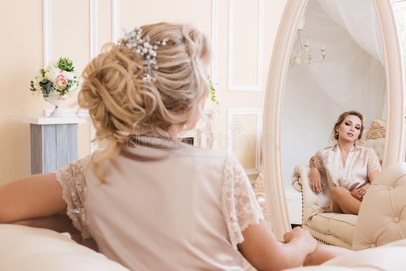 Sch?ne junge sexy Blondine in einer Seidenrobe, die auf einem Sofa vor dem Spiegel sitzt stockfotos