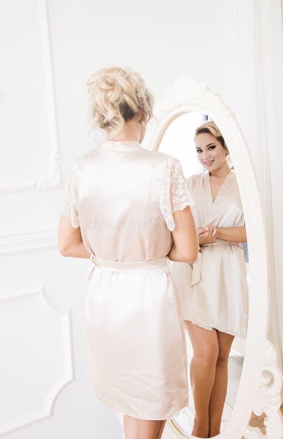 Sch?ne junge sexy Blondine in einer Seidenrobe stehen vor dem Spiegel lizenzfreies stockbild