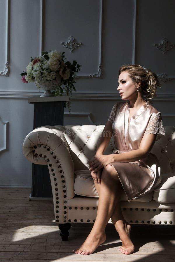 Sch?ne junge sexy Frauenblondine in einer Seidenrobe sitzt auf dem Sofa gegen?ber von dem Fenster in den Strahlen des Vorfalllich stockfoto