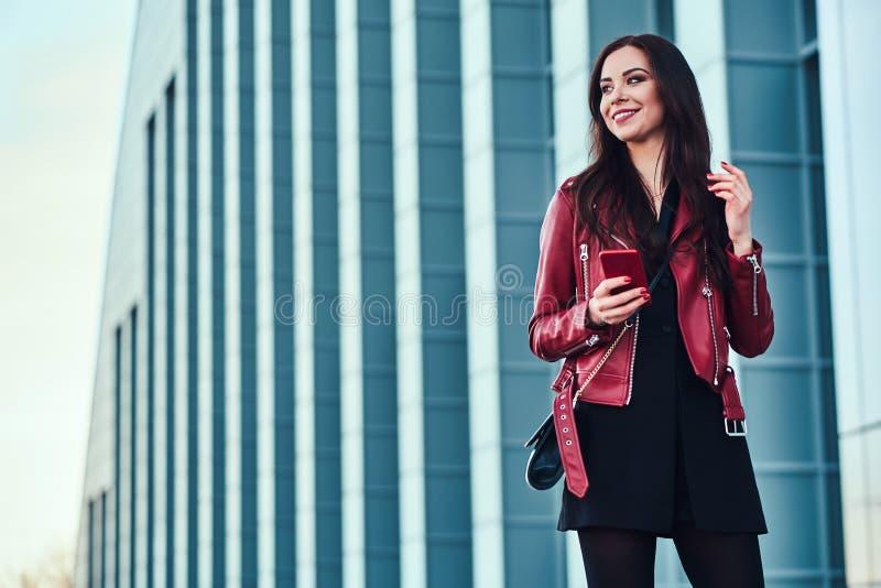 Sch?ne l?chelnde Frau in der roten Jacke steht nahe bei Geb?ude mit Smartphone in ihren H?nden stockbilder