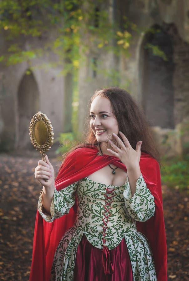 Sch?ne l?chelnde Frau im langen mittelalterlichen Kleid mit Spiegel stockbilder