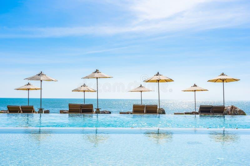 Sch?ne Landschaft von Seeozean auf Himmel mit Regenschirm und von Stuhl um Luxusswimmingpool im Freien stockbilder