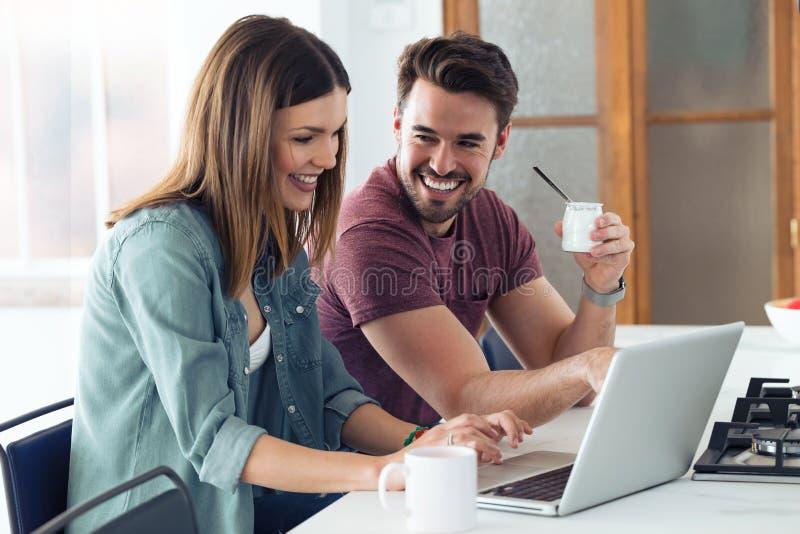 Sch?ne reizende junge Paare unter Verwendung ihres Laptops und haben Fr?hst?cks in der K?che zu Hause lizenzfreie stockbilder