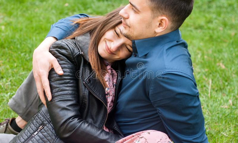 Sch?ne romantische Paare, die am Fr?hlingsgr?npark umfassen lizenzfreie stockfotos