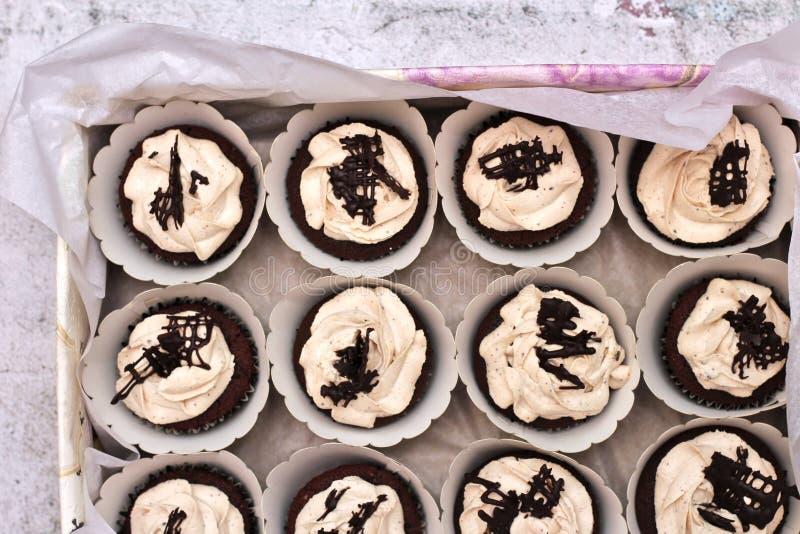 Sch?ne Schokoladencreme bedeckte kleine Kuchen in einem wei?en Kasten, der mit einem Seil auf einem konkreten Hintergrund gebunde stockbild