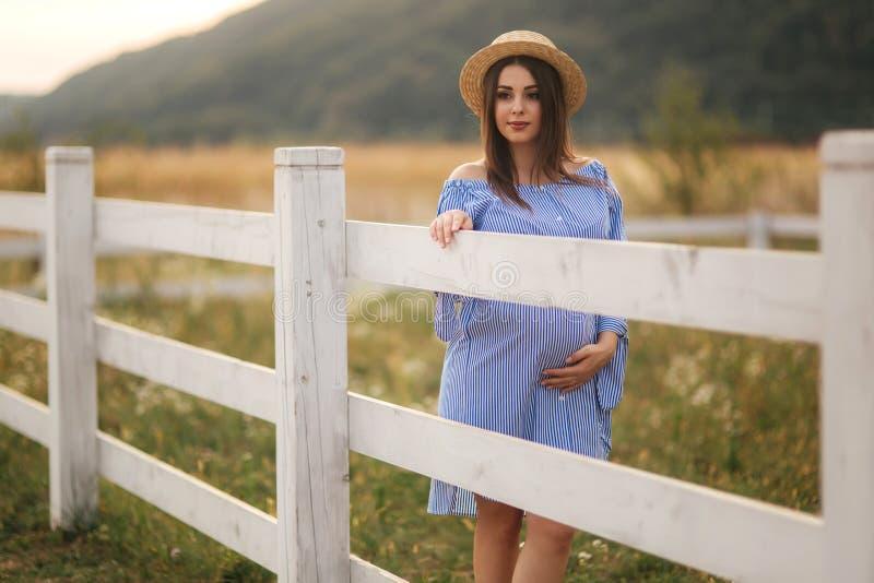 Sch?ne schwangere Frau im blauen Kleid und Strickm?tze stehen nahe dem fance im Bauernhof Sie setzte H?nde auf ihren Bauch und stockfoto
