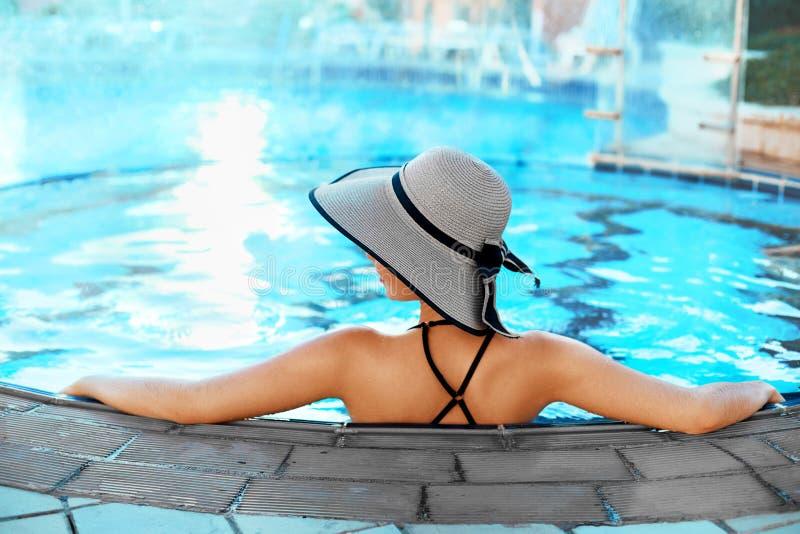 Sch?ne sexy Frau, die im Swimmingpool-Wasser sich entspannt M?dchen mit gesunder gebr?unter Haut, stockfoto