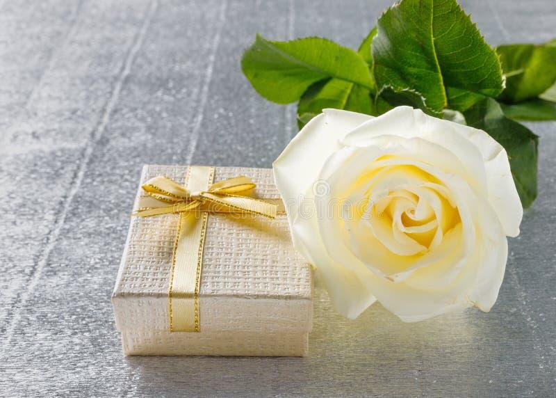 Sch?ne wei?e Rose mit einer goldenen Geschenkbox f?r Valentinstag stockfotografie