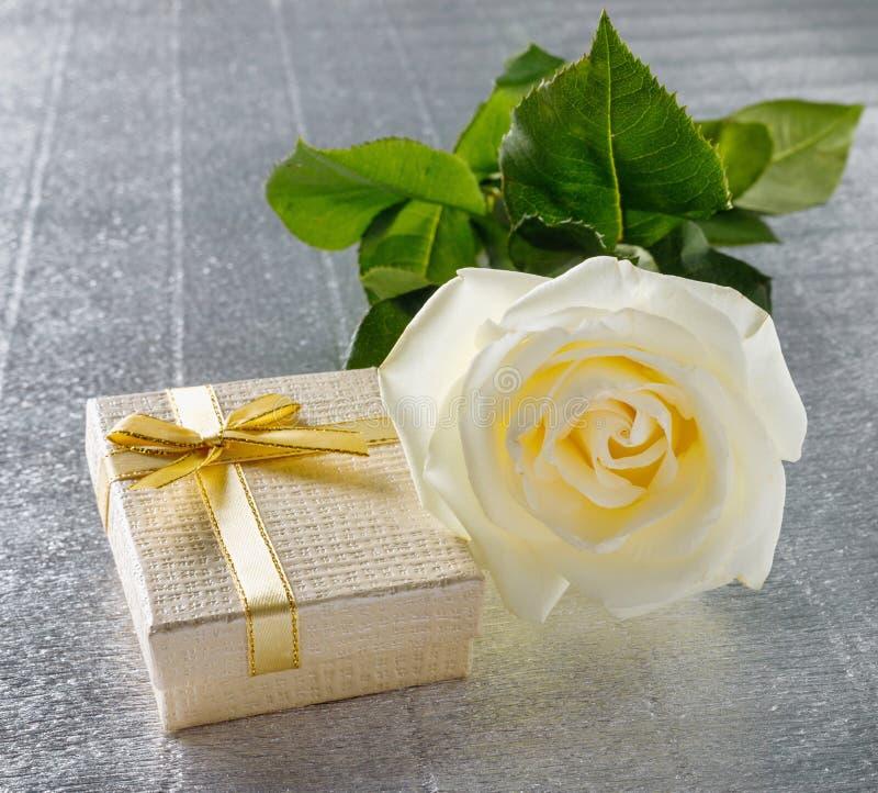 Sch?ne wei?e Rose mit einer goldenen Geschenkbox f?r Valentinstag lizenzfreies stockbild