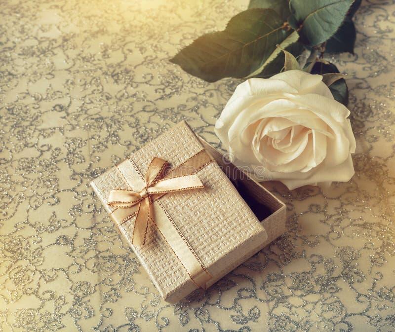 Sch?ne wei?e Rose mit einer goldenen Geschenkbox f?r Valentinstag stockfoto