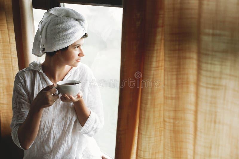 Sch?ner gl?cklicher trinkender Kaffee oder Tee der jungen Frau, sitzend am gro?en h?lzernen Fenster im Hotelzimmer- oder Ausgangs lizenzfreie stockbilder