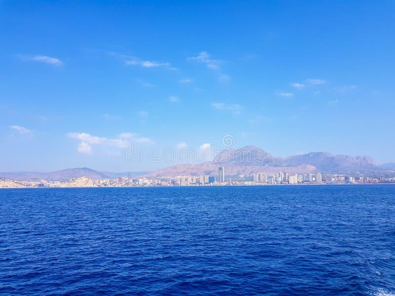 Sch?ner Levante-Strand in Benidorm, Spanien Bild genommen vom Meer, mit den Skylinen von Wolkenkratzern und einem Boot des ersten stockbild