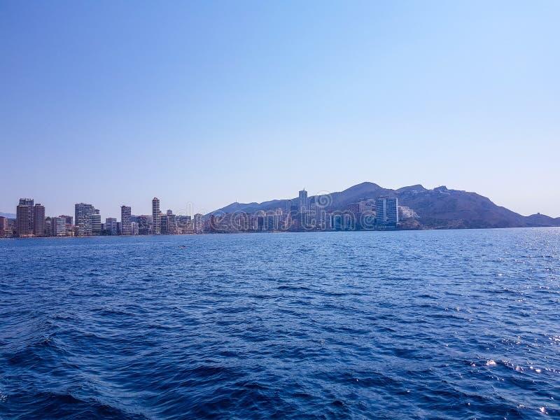 Sch?ner Levante-Strand in Benidorm, Spanien Bild genommen vom Meer, mit den Skylinen von Wolkenkratzern und einem Boot des ersten lizenzfreie stockfotos