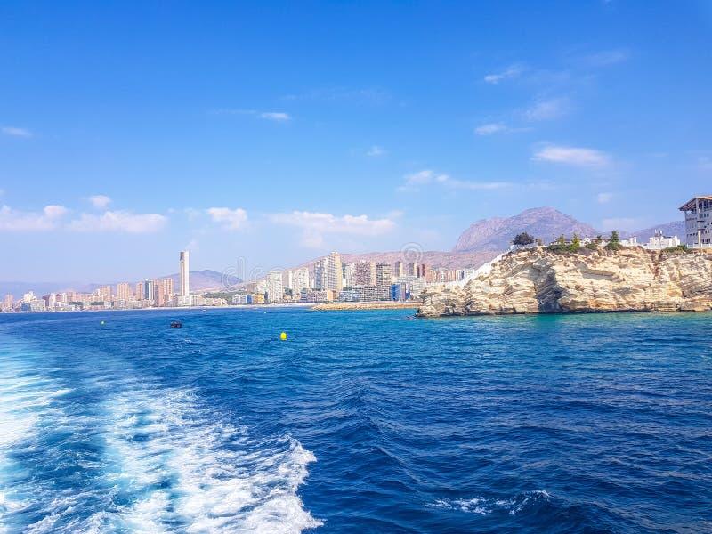 Sch?ner Levante-Strand in Benidorm, Spanien Bild genommen vom Meer, mit den Skylinen von Wolkenkratzern und einem Boot des ersten stockfotografie
