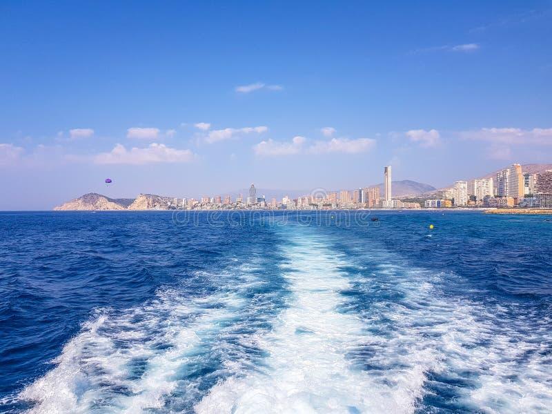 Sch?ner Levante-Strand in Benidorm, Spanien Bild genommen vom Meer, mit den Skylinen von Wolkenkratzern und einem Boot des ersten stockbilder