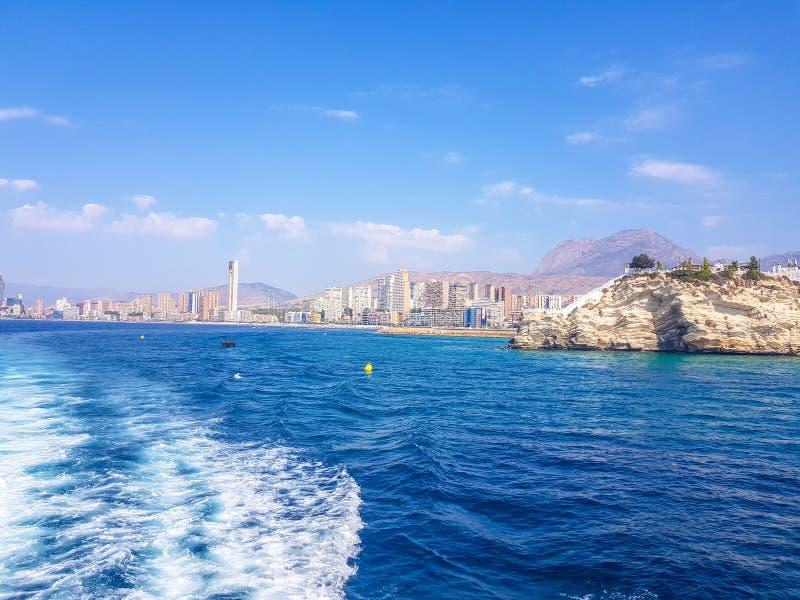 Sch?ner Levante-Strand in Benidorm, Spanien Bild genommen vom Meer, mit den Skylinen von Wolkenkratzern und einem Boot des ersten lizenzfreies stockfoto
