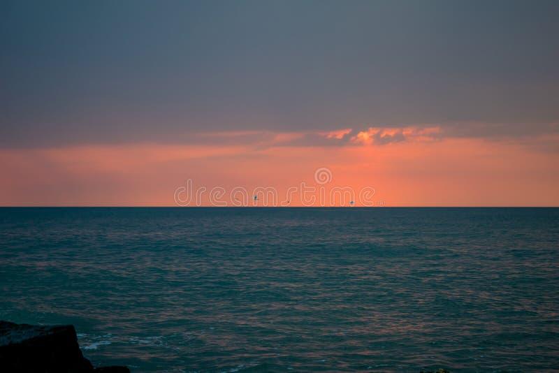 Sch?ner Sonnenaufgang auf dem Ozean Boot und Felsen nahe dem Ufer Schw?ne im Flug lizenzfreie stockfotografie