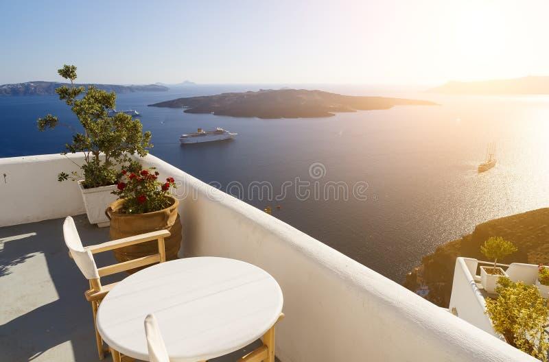 Sch?ner Sonnenuntergang in Santorini-Insel, Griechenland Zwei Stühle auf Terrasse mit Seeansicht lizenzfreies stockbild