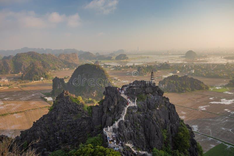 Sch?ner Sonnenunterganglandschaftsstandpunkt mit wei?em stupa von der Spitze des M.U.A.-H?hlenberges, Ninh Binh, Tam Coc, Vietnam stockbilder