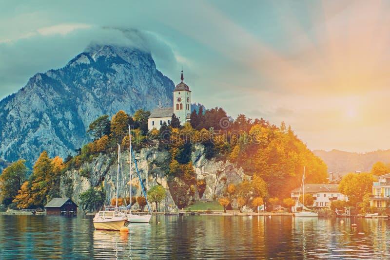 Sch?ner szenischer Sonnenuntergang ?ber ?sterreichischem Alpensee Boote, Yachten im Sonnenlicht vor Kirche auf dem Felsen mit Wol stockbilder