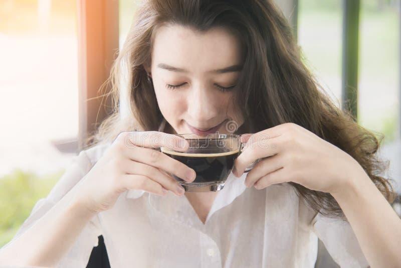 Sch?ner trinkender Kaffee der jungen Frau, der am Fenster im Haus sitzt trinkender Kaffee der attraktiven jungen asiatischen Frau stockbilder