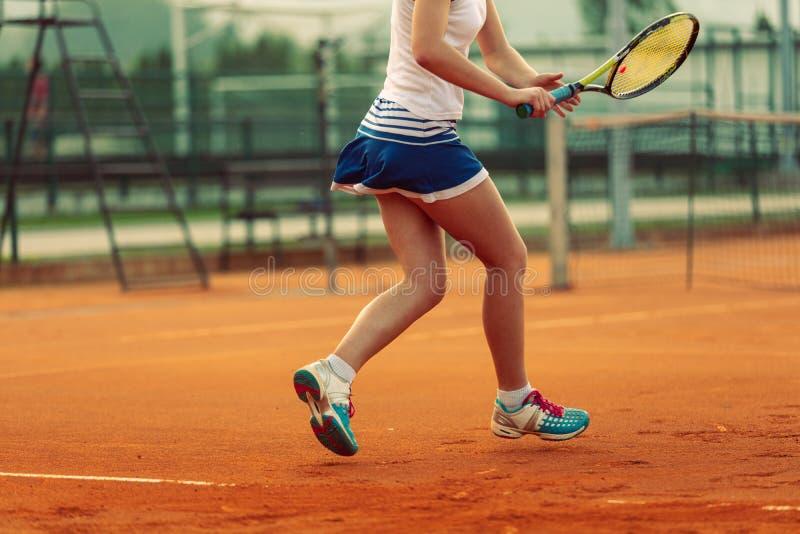 Sch?ner weiblicher Athlet mit dem perfekten K?rper, der oben auf Tennisplatz, Abschluss aufwirft lizenzfreie stockbilder