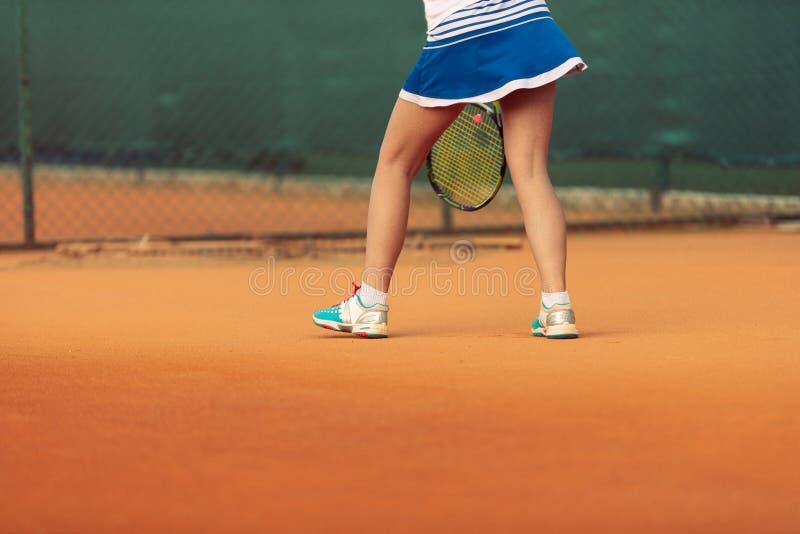 Sch?ner weiblicher Athlet mit dem perfekten K?rper, der oben auf Tennisplatz, Abschluss aufwirft stockfotos