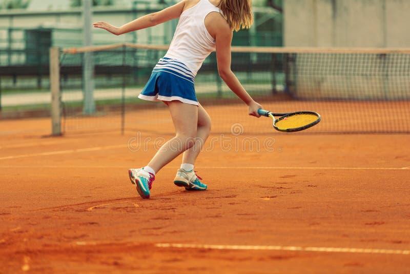 Sch?ner weiblicher Athlet mit dem perfekten K?rper, der oben auf Tennisplatz, Abschluss aufwirft stockfoto