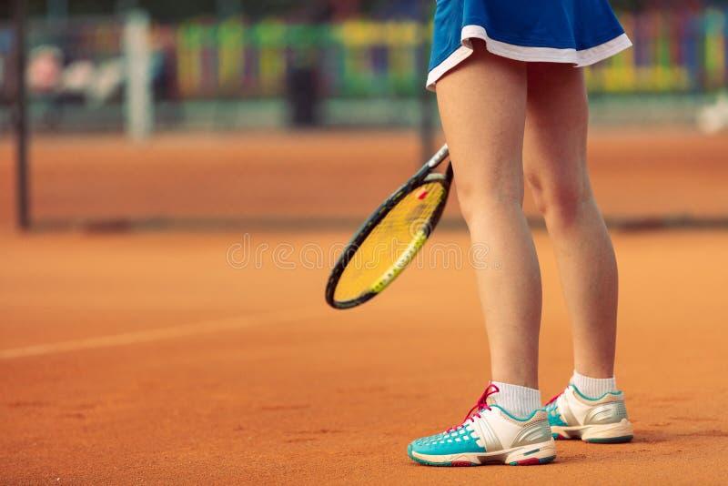 Sch?ner weiblicher Athlet mit dem perfekten K?rper, der oben auf Tennisplatz, Abschluss aufwirft stockbild