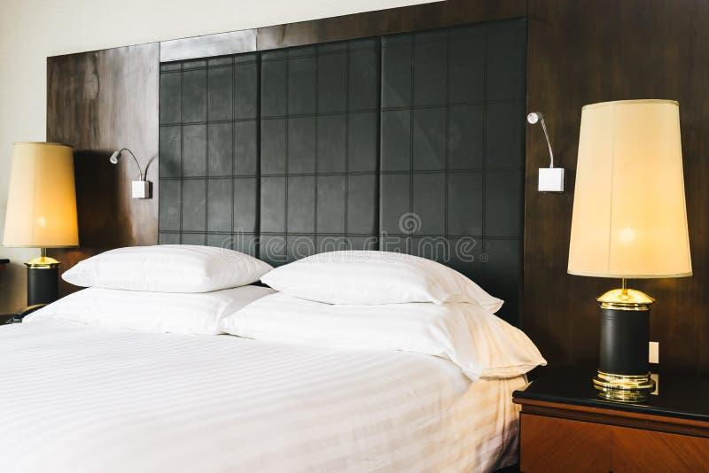 Sch?nes bequemes wei?es Luxuskissen und Decke auf Bett mit heller Lampe stockfoto