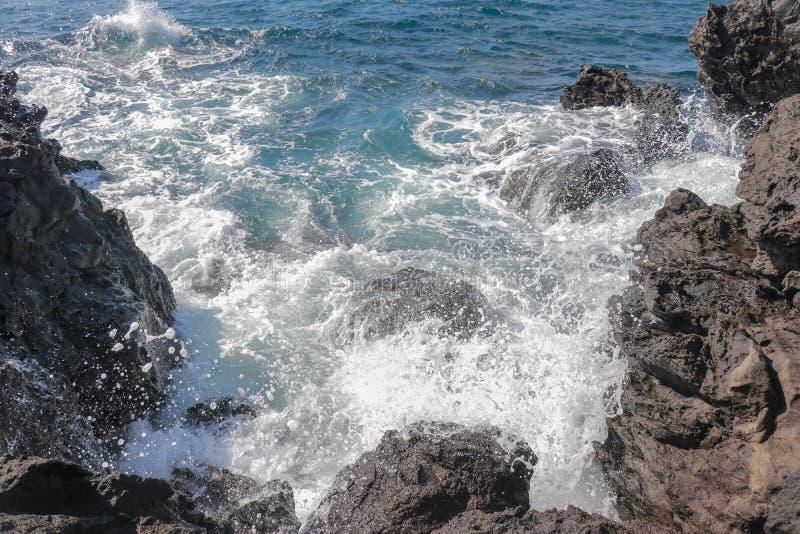 Sch?nes blaues Meer und ein Strand mit enormen Steinbl?cken Gefahrenseewelle, die auf Felsenk?ste mit Spray und Schaum zusammenst stockfotos