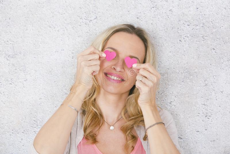 Sch?nes, blondes und sexy M?dchen wirft mit zwei Rosa, Papierherzen vor grauem, konkretem Hintergrund auf lizenzfreie stockfotografie
