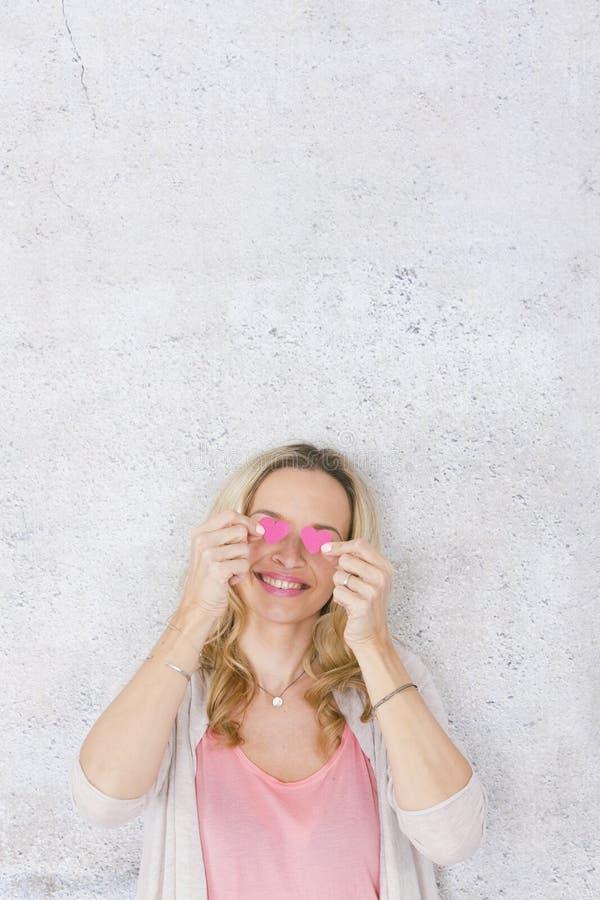 Sch?nes, blondes und sexy M?dchen wirft mit zwei Rosa, Papierherzen vor grauem, konkretem Hintergrund auf stockbilder