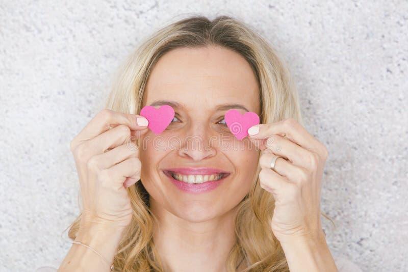 Sch?nes, blondes und sexy M?dchen wirft mit zwei Rosa, Papierherzen vor grauem, konkretem Hintergrund auf lizenzfreie stockbilder