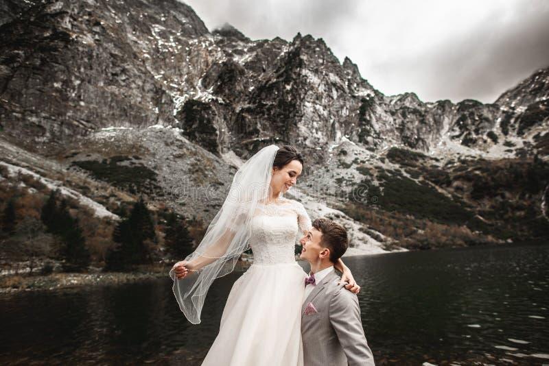 Sch?nes Heiratsphotosession Der Br?utigam kreist seine junge Braut, auf dem Ufer des Sees Morskie Oko ein polen stockbilder
