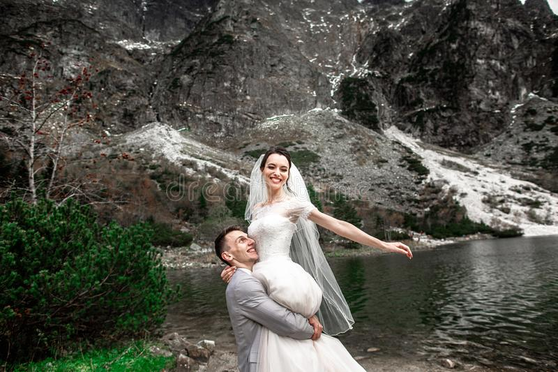 Sch?nes Heiratsphotosession Der Br?utigam kreist seine junge Braut, auf dem Ufer des Sees Morskie Oko ein polen stockfotografie