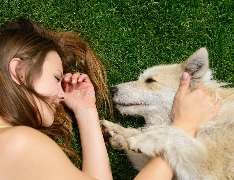 Sch?nes junges gl?ckliches Lachenm?dchen, das mit ihrem Hund im Freien spielt lizenzfreie stockfotografie