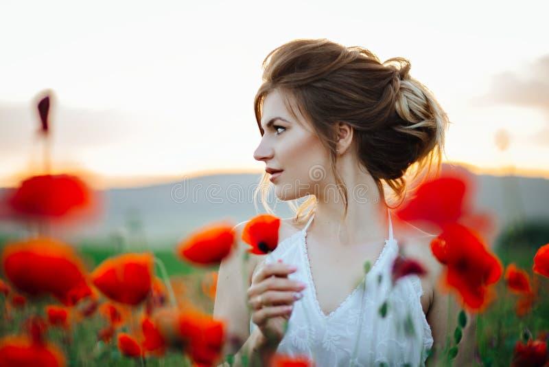 Sch?nes junges M?dchen auf den Mohnblumengebieten bei Sonnenuntergang Sch?ne Natur stockbild
