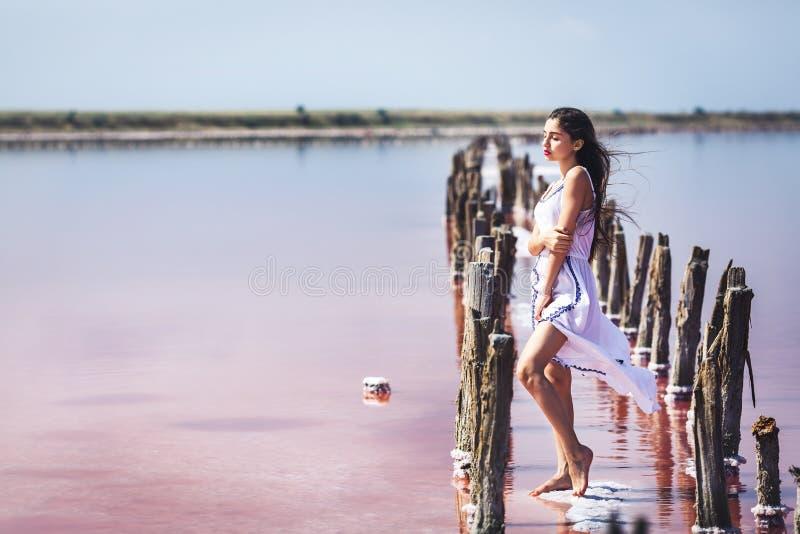 Sch?nes junges M?dchen im langen wei?en Kleid, das auf salzigem rosa See aufwirft stockbilder