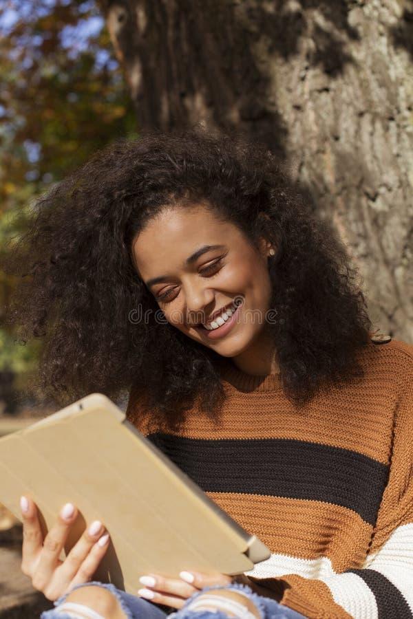 Sch?nes junges M?dchen mit dem dunklen gelockten Haar unter Verwendung des Tablet-Computers, im Freien lizenzfreie stockbilder