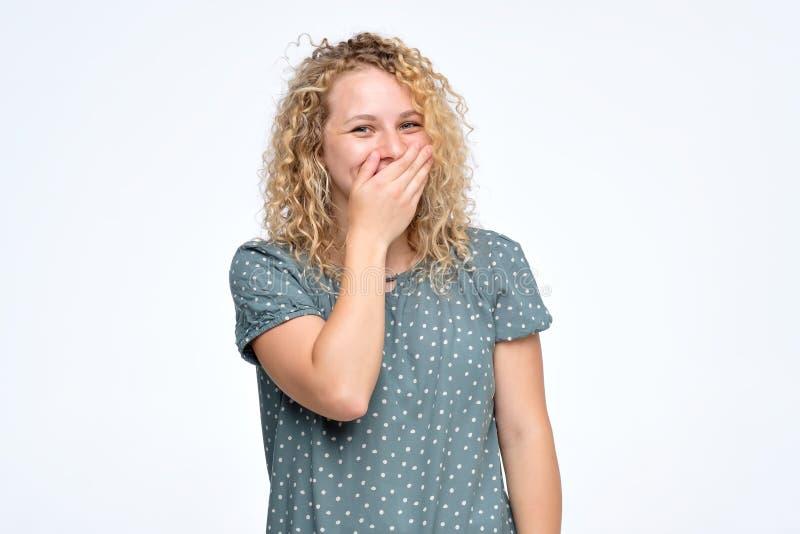 Sch?nes junges weibliches Gekicher froh, bedeckt Mund, w?hrend Versuche aufh?ren zu lachen stockfoto