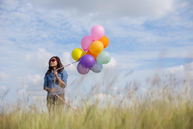 Sch?nes M?dchen, das mit Ballonen auf dem Strand springt lizenzfreies stockfoto