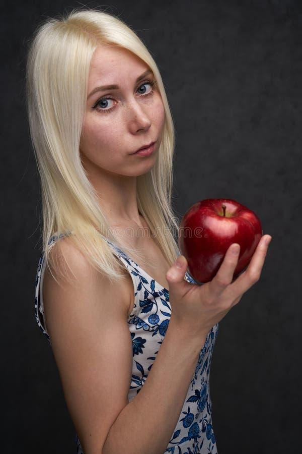 Sch?nes M?dchen in einer modischen Kleidung mit Apfel lizenzfreies stockfoto