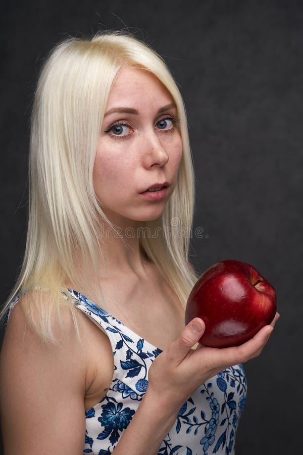 Sch?nes M?dchen in einer modischen Kleidung mit Apfel stockfotografie