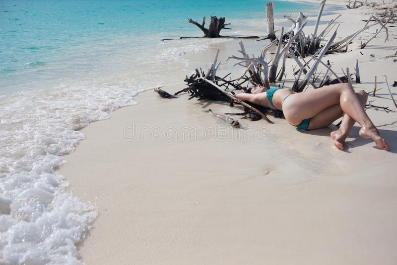 Sch?nes M?dchen im Bikini, der unter h?lzernen Dornen auf Strand liegt stockfotos
