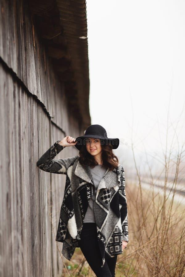 Sch?nes M?dchen mit dem langen Haar und schwarzem Hut, St?nde auf dem Hintergrund des alten Holzhauses der Weinlese lizenzfreies stockbild