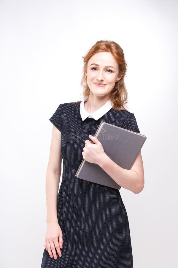 Sch?nes M?dchen mit dem roten Haar und grauem Buch in den H?nden kleidete im schwarzen Kleid auf Wei? lokalisiertem Hintergrund a lizenzfreie stockfotografie